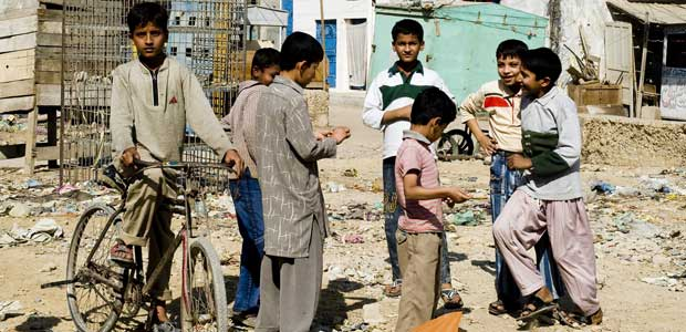 Boys stand talking in an undeveloped playground in Karachi, Pakistan.