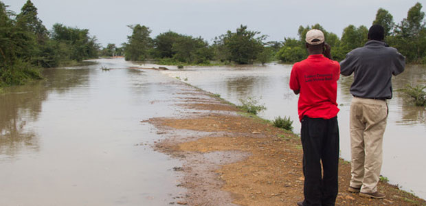Men survey a flooded road in Kenya.