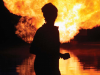 Woman silhouetted in front of gas flare