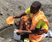 A woman scoops water in a dry riverbed