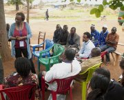 A man stands as he speaks to a seated group of people surrounding him