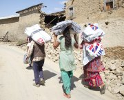 Women carrying emergency shelter kits