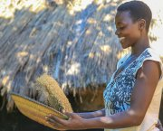 Evelyne  Flora Latabu shaking a bowl of grains.
