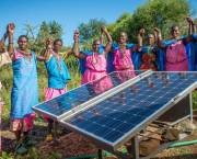 A community-based green energy project: Sinteyo and the women's group with solar panels at the greenhouse in Isiolo, Kenya (Photo: Annie Bungeroth/CAFOD)