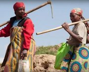 Two women carrying farming tools