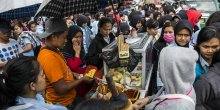 A food vendor is surrounded by people in a busy street