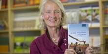 Camilla Toulmin holding her new book