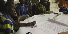 Delegates at CBA12 in Malawi gather around a table and write on a document