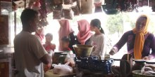 An Indonesia market trader stands at his stall while women customers look at the food on sale