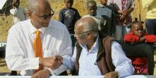 Jockin Arputham, right, signs documents with Stellenbosch Mayor Sidego in South Africa