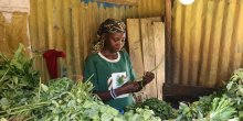 A woman behind a counter arranges her vegetable produce