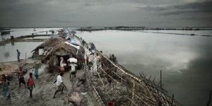 People build temporary shelters on the edge of the Bay of Bengal following a cyclone and flooding