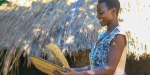 Evelyne  Flora Latabu shaking a bowl of grains.