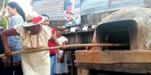 A women puts food into an outdoor oven