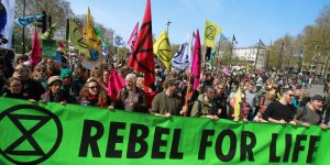 Extinction Rebellion climate protesters march through London behind a big green banner proclaiming 'Rebel for life'