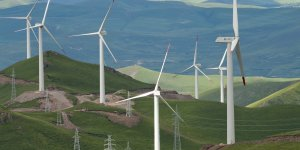 Wind power turbines and electricity pylons alongside one another in China