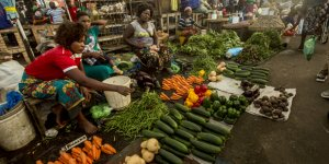 Women traders on a market stall, with rows of different fruit and vegetables in front of them