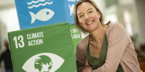 Tara Shine is photographed smiling next to boxes on which is written 'climate action'