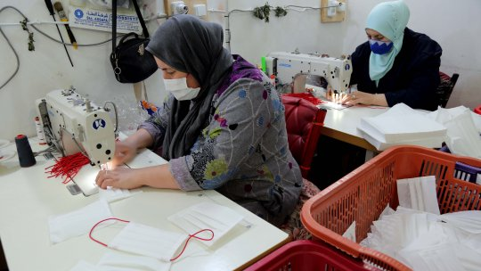 Two women sewing face masks