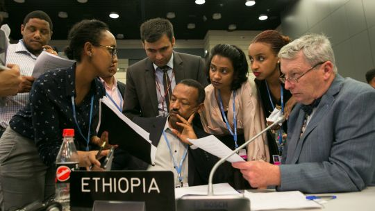 Delegates from the LDC Group, including chair Gebru Jember Endalew and IIED's Achala Abeysinghe discuss the revised APA text, Bonn, May 2017 (Photo: IISD/ENB/Kiara Worth)