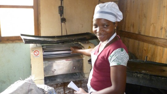 A woman wearing a chef's uniform and hat poses in front of a breadmaking machine