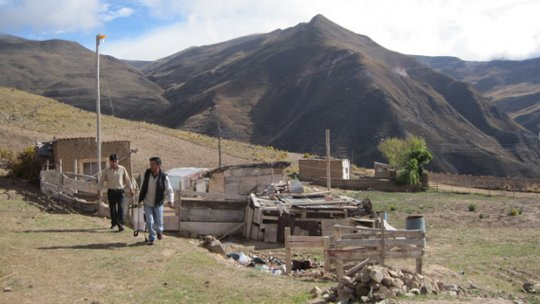 Two men stand in front of a building under construction, with mountains in the background