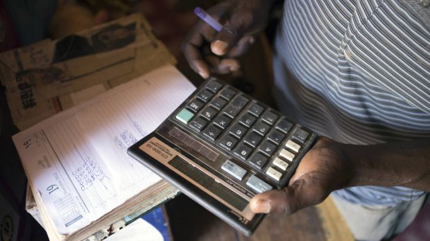 A merchant calculates costs in Geita District, Tanzania (Photo: Brian Sokol/Panos Pictures)